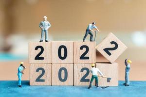 equipe de trabalho de pessoas em miniatura cria bloco de madeira número 2022 foto