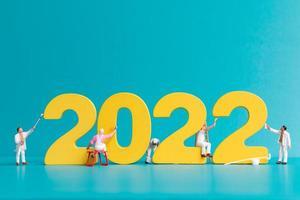 equipe de trabalho de pessoas em miniatura, pintura número 2022 foto