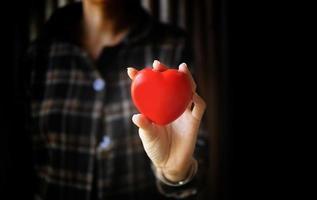 mulher com as mãos segurando um coração vermelho. conceito de seguro de saúde do coração. foto