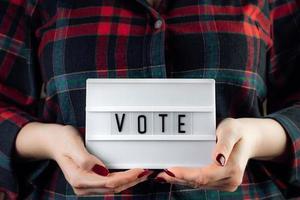 mulher tem cartaz nas mãos. votação online e conceito de eleições. foto