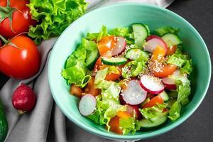 salada de vegetais sazonal de produtos agrícolas orgânicos em fundo cinza. mistura de tomates, pepinos e rabanetes. foto