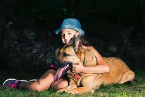 uma menina abraça seu cão pastor alemão foto