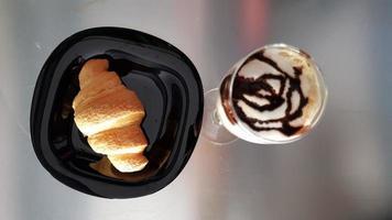 pãozinho no prato preto e copo de milk-shake foto