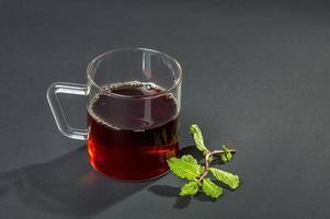 xícara de chá, hortelã e limão em fundo escuro foto