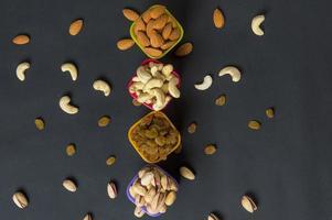 mistura saudável de frutas secas e nozes em fundo escuro. amêndoas, pistache, castanha de caju, passas foto