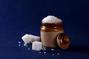 açúcar. açúcar granulado branco e açúcar refinado em um fundo azul foto