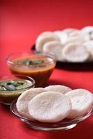 idli com sambar e chutney de coco em fundo vermelho, prato indiano comida favorita do sul da índia rava idli ou semolina à toa ou rava à toa, servido com sambar e chutney verde. foto