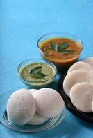idli com sambar e chutney de coco no fundo azul, prato indiano comida favorita do sul da Índia rava idli ou semolina à toa ou rava à toa, servido com sambar e chutney de coco verde. foto