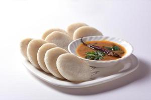 idli com sambar e chutney de coco, prato indiano comida favorita do sul da índia rava idli ou semolina à toa ou rava à toa, servido com sambar e chutney de coco verde. foto