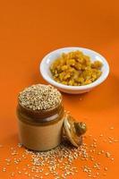 sementes de gergelim em panela de barro com açúcar mascavo na tigela foto
