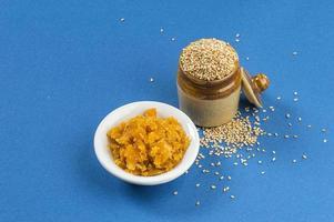 sementes de gergelim em uma panela de barro com açúcar mascavo em uma tigela sobre fundo azul foto