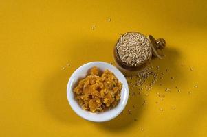 sementes de gergelim em uma panela de barro com açúcar mascavo em uma tigela sobre fundo amarelo foto