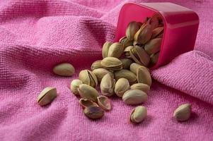 pistache em recipiente em fundo rosa foto