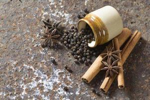 especiarias e ervas. alimentos e ingredientes da cozinha. paus de canela, estrelas de anis, pimenta preta em plano de fundo texturizado foto