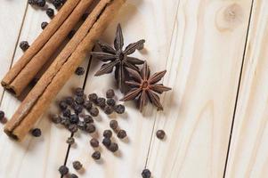especiarias e ervas. alimentos e ingredientes da cozinha. paus de canela, estrelas de anis e pimenta preta em um fundo de madeira. foto