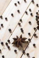 especiarias e ervas. alimentos e ingredientes da cozinha. estrelas de anis e pimenta preta em um fundo de madeira. foto