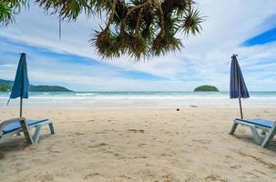 praia de areia de verão com cadeira de praia e ondas foto