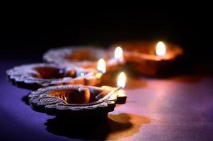 lâmpadas de lanterna diya de argila coloridas acesas durante a celebração do diwali projeto de cartão de cumprimentos festival indiano luz hindu chamado diwali. foto