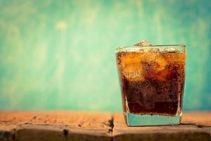 bebida de cola na madeira foto