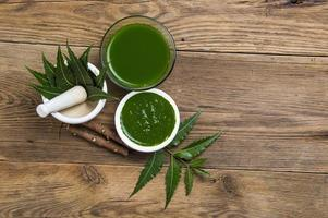folhas de nim medicinal em almofariz e pilão com pasta de nim, suco e galhos em fundo de madeira foto