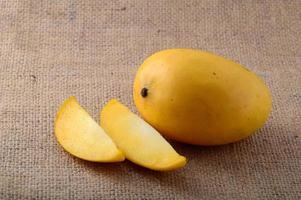 fruta da manga com uma fatia no fundo do pano de saco foto