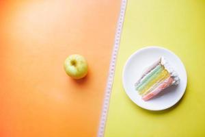 fita métrica, maçã verde e um bolo de padaria na cor de fundo foto