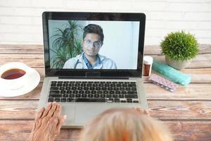 consulta online com médico no laptop e segurando um recipiente de pílulas médicas foto
