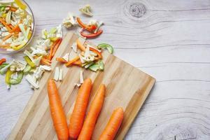 cenouras frescas na tábua de cortar na mesa foto