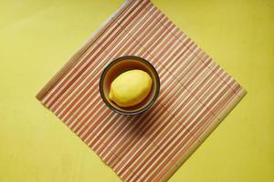 limão amarelo em uma tigela sobre fundo amarelo com espaço de cópia. foto