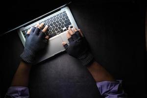 mão de hacker roubando dados de laptop de cima para baixo foto