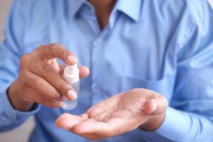 close-up da mão do jovem usando spray desinfetante para as mãos. foto