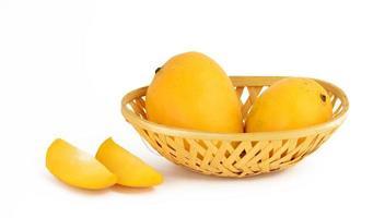 fruta de manga na cesta com uma fatia no fundo branco foto