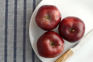 deliciosas maçãs no prato com faca na toalha de mesa listrada foto