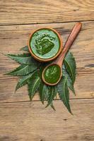 folhas de nim medicinal com pasta em fundo de madeira foto