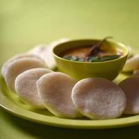 idli com sambar em uma tigela sobre fundo verde, prato indiano comida favorita do sul da Índia rava idli ou semolina à toa ou rava à toa, servido com sambar e chutney de coco verde. foto