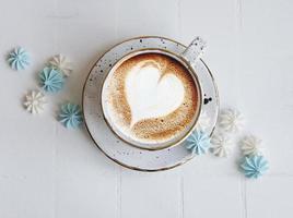 xícara com café e pequenos merengues foto