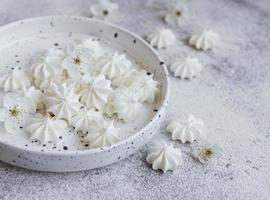 pequenos merengues brancos na tigela de cerâmica foto