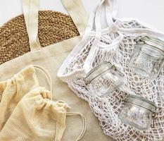 saco de malha, sacos de algodão e potes de vidro foto