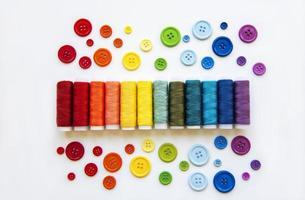 carretéis de linha e botões nas cores do arco-íris foto