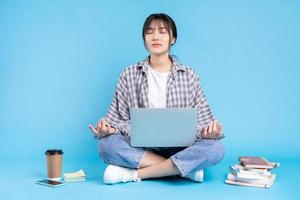 aluna asiática com expressão lúdica no fundo azul foto