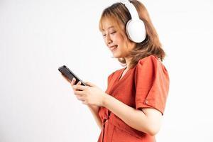 jovem asiática usando seu telefone e usando fones de ouvido para curtir música foto