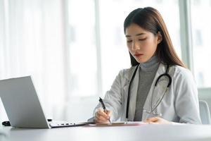 médica asiática está trabalhando na clínica foto