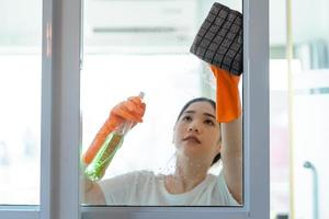linda mulher asiática limpando a porta de vidro do quarto foto