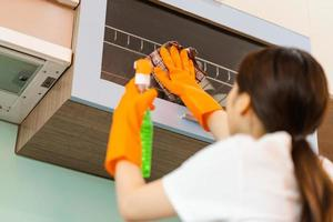 linda mulher asiática limpando armários de cozinha foto