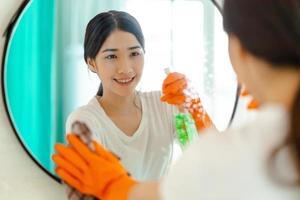 linda mulher asiática limpando espelho no banheiro foto