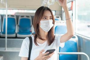 menina asiática usando máscara enquanto usa smartphone no ônibus foto