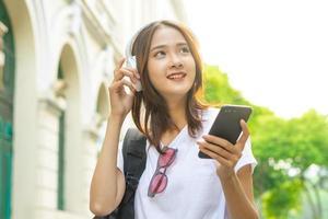 jovem asiática lendo texto em seu telefone e usando fones de ouvido para ouvir música na rua foto