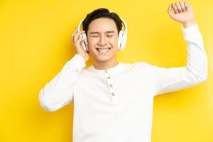 foto de homem asiático de camisa branca ouvindo música com os olhos fechados em fundo amarelo
