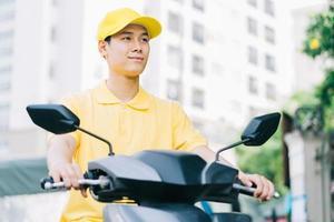 entregador asiático está dirigindo sua motocicleta para entregar ao cliente foto