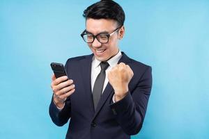 Homem de negócios asiático vestindo terno usando smartphone e sente vitória foto